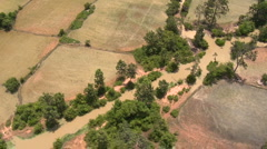 Aerial of different rural fields with river flowing through low altitude Stock Footage