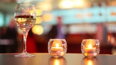 Candles putted inside glass and goblet filled with wine stand on table Stock Footage