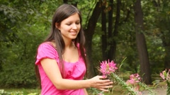 Good looking woman smell some flower in park Stock Footage