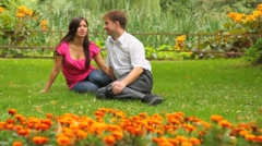 Couple sitting in park amid flowers Stock Footage