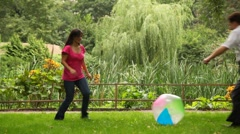 Couple plays with ball near fence in park Stock Footage