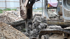 Crane breaking up concrete into pieces to level the ground. Stock Footage