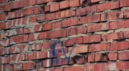 Stock Video Footage of Red old brick's wall with graffiti running up