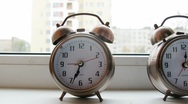 Two alarm clocks on a window sill at morning. Stock Footage
