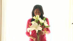 Young woman smelling flowers Stock Footage