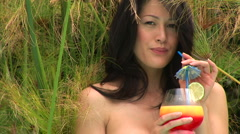 Portrait of young woman in sarong sipping a tropical drink Stock Footage