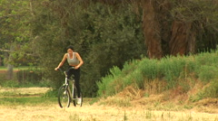 Young woman riding a bicycle in rural setting Stock Footage