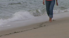 Young woman walking along ocean shore line Stock Footage