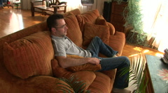 Young man on couch using remote to watch TV - stock footage
