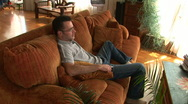 Young man on couch using remote to watch TV Stock Footage