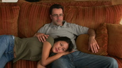 Young couple on couch snuggling while watching TV Stock Footage