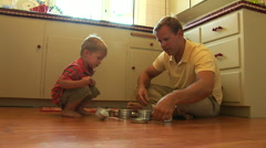 Father playing with toddler son on kitchen floor Stock Footage