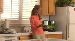 Young woman on a diet eating celery in the kitchen Stock Footage