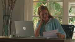 Young woman happily working at home with laptop - stock footage