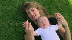 Mother and baby outdoors laying in grass Stock Footage
