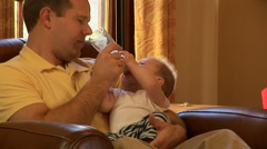 Young father feeding baby son bottle of milk at Christmas time Stock Footage