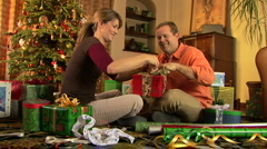 Young couple wrapping Christmas presents by the tree Stock Footage