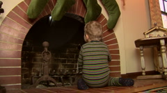 Toddler in pajamas looking for Santa in the fireplace at Christmas Stock Footage