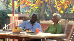 Senior couple having coffee and breakfast outdoors on the patio - stock footage