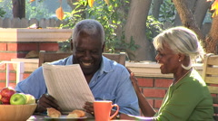 Close up of senior couple having coffee and breakfast outdoors on the patio - stock footage