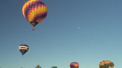 Six hot air balloons rise below full moon Stock Footage