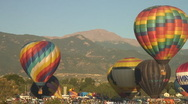 Stock Video Footage of two hot air balloons rise in front of Pikes Peak