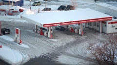 In winter city cars refuel at petrol station Stock Footage