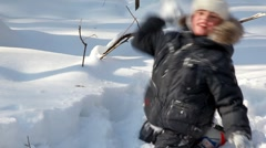 Boy walks and plays snowballs in winter wood Stock Footage