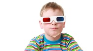 Boy sits in anaglyph glasses for viewing stereo images Stock Footage