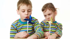 Girl and boy with chocolate-smeared mouth sit at desk and blow into plastic Stock Footage