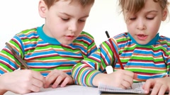 Girl and boy with a chocolate-smeared mouth draw pictures in notebooks Stock Footage