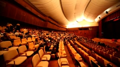 People sit in auditorium for watching performance of hypnotist - stock footage