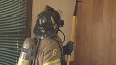 Firefighters breaking out ceiling and spraying water Stock Footage
