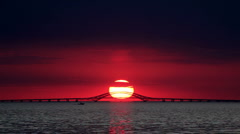 Big Red Sun Setting Over Bridge with Boat Stock Footage