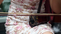 Chinese girl wearing a cheongsam playing the national instrument - Erhu Stock Footage