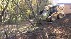 Mini loader pushing tree down Stock Footage