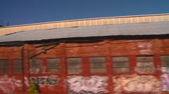 Passing graffiti covered abandoned warehouses, from rail perspective  Stock Footage
