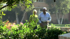 Senior couple walking together through backyard - stock footage