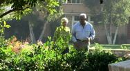 Senior couple walking together through backyard Stock Footage