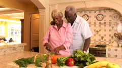 Senior couple at home in kitchen cutting fresh vegetables - stock footage