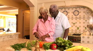 Senior couple at home in kitchen cutting fresh vegetables Stock Footage
