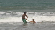 Stock Video Footage of young man teaching boy to surf