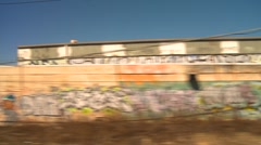 Passing graffiti covered warehouses and home, rail travel perspective Stock Footage