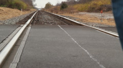 Man running on rail road tracks Stock Footage