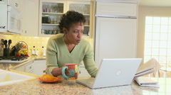 Woman in kitchen on laptop drinking coffee Stock Footage