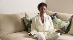 Woman on sofa meditating Stock Footage
