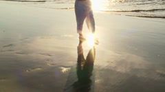 Young woman walking in sand by seaside at sunset Stock Footage
