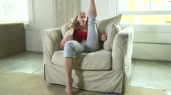 Woman acting goofy in chair - stock footage