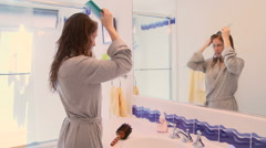 Woman in bathroom combing washed hair Stock Footage
