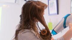 Woman in bathroom curling hair Stock Footage
